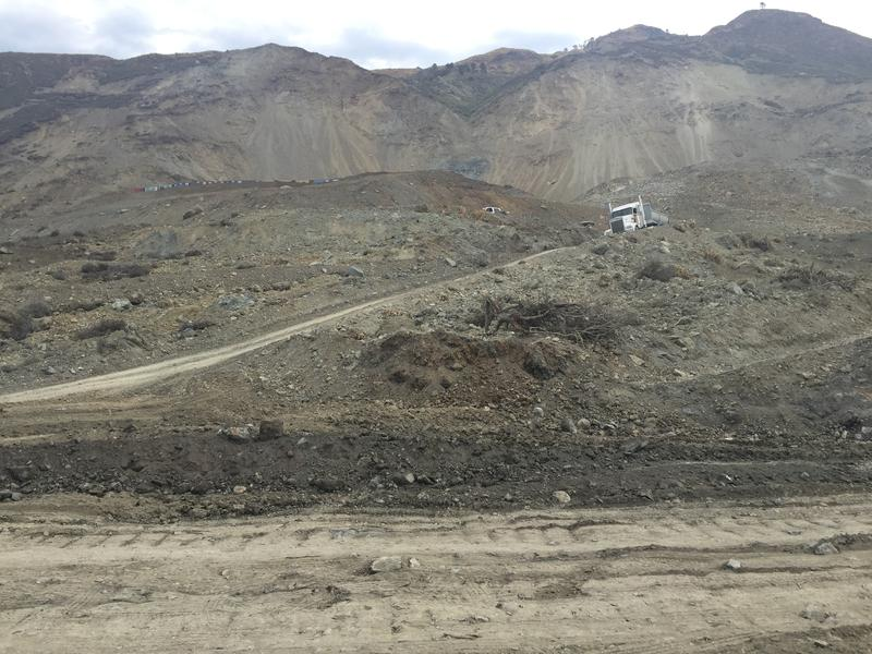 A semitruck hauling boulders drives down the slope of land added to the coast by the Mud Creek Slide.