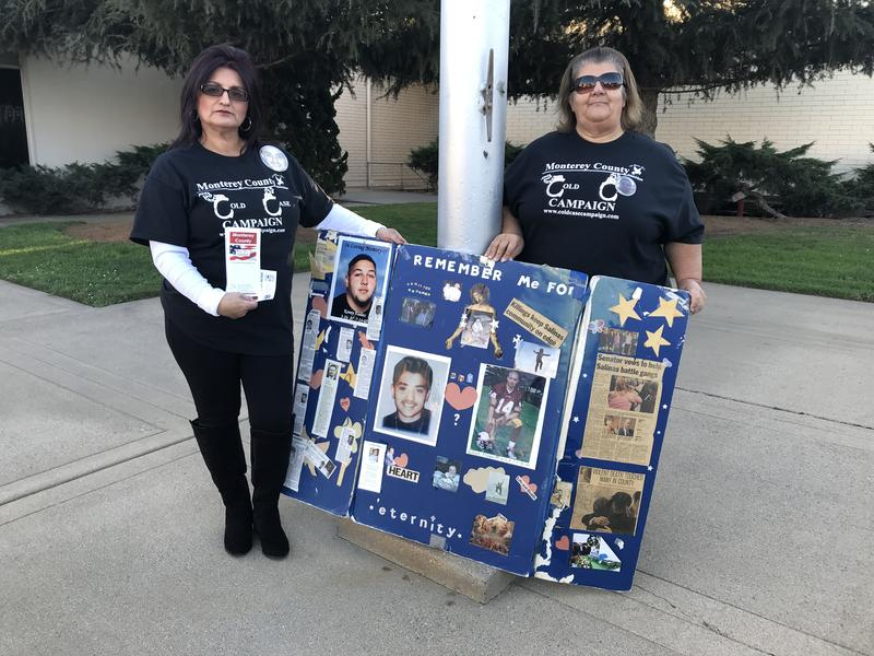 Debbie Aguilar (left) holds a poster with pictures of her son Stephen. He was murdered in 2002. The case remains unsolved. But she hopes to change that with a new website.