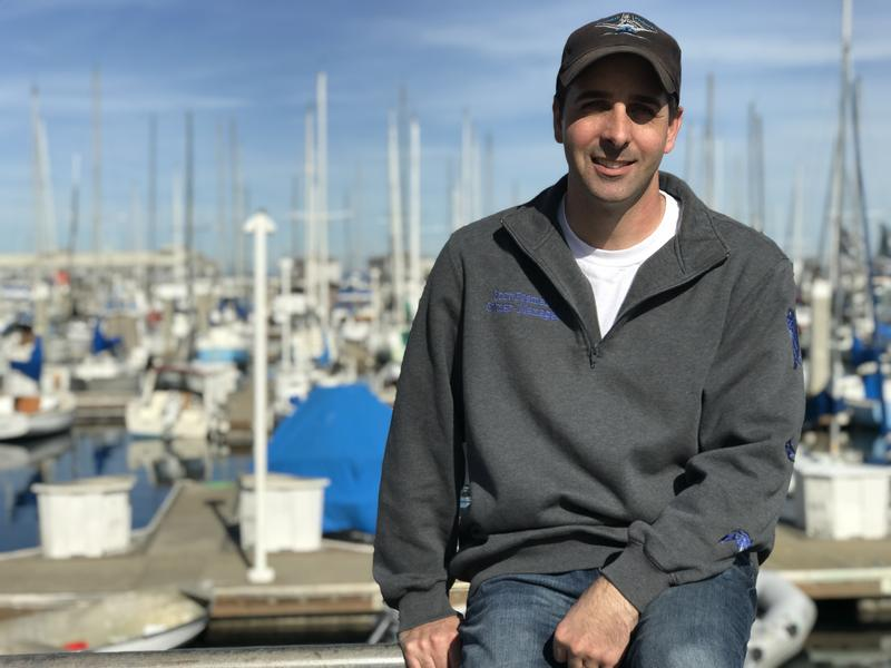 Fisherman Scott Fosmark sits on a railing in front of the Monterey Municipal Marina. With deep roots in Monterey's fishing heritage, he hopes the new fish hub can restore the area's local fish supply chain.