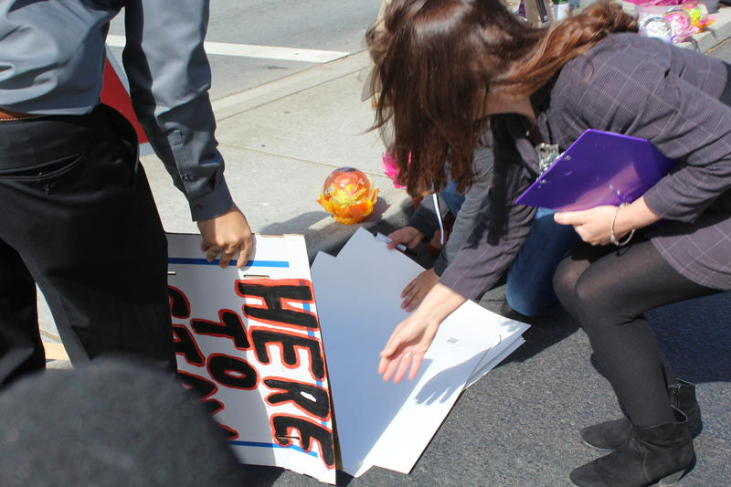 Local activist Kim Snyder brought paper and markers for people to make signs.