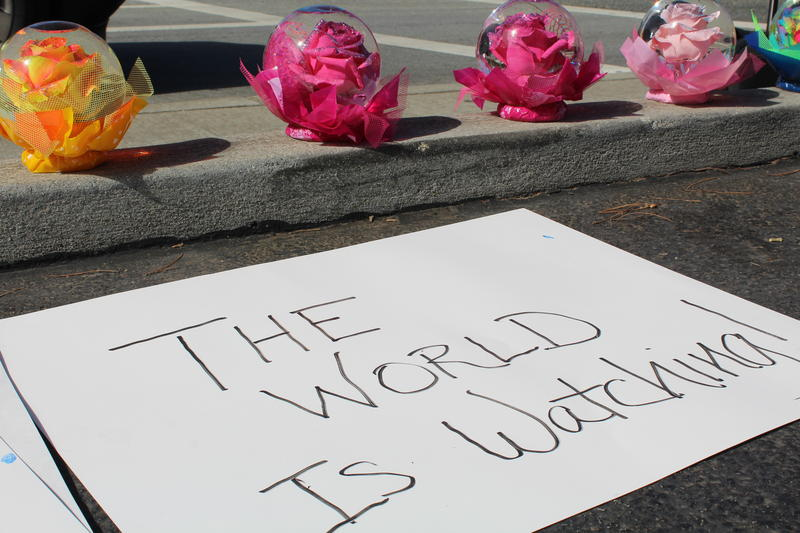 One of the signs read, 'The World is Watching.'