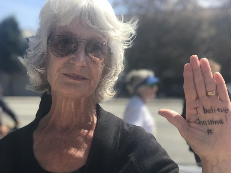 """Marianne Wieland was one of nearly 70 people who gathered in downtown Santa Cruz Thursday. She and several others wrote """"I believe Christine"""" on their palms."""