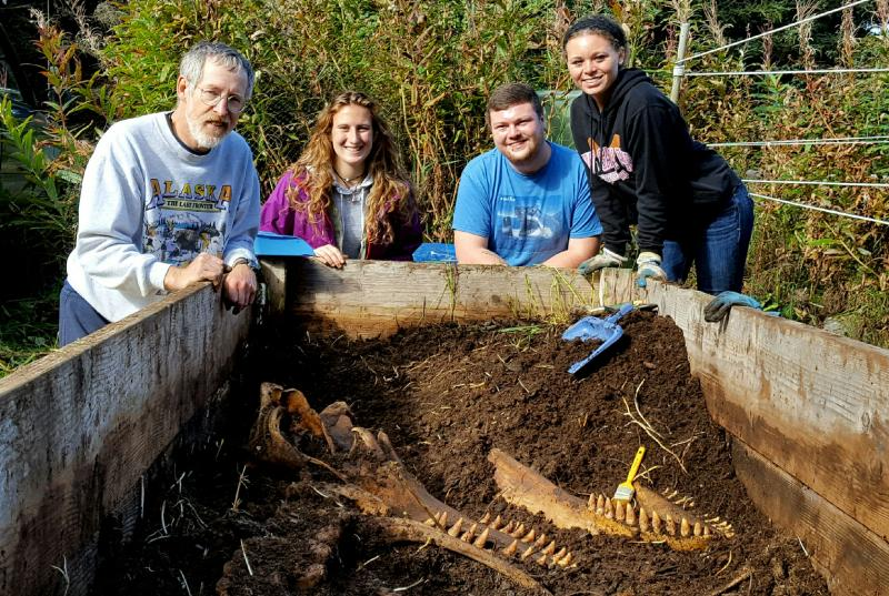 Instructor Lee Post, along with students Jamie Knaub, Chris Walker and Molly Mays. The excavation crew dug up the orca skeleton, which had been buried for two years in horse manure.
