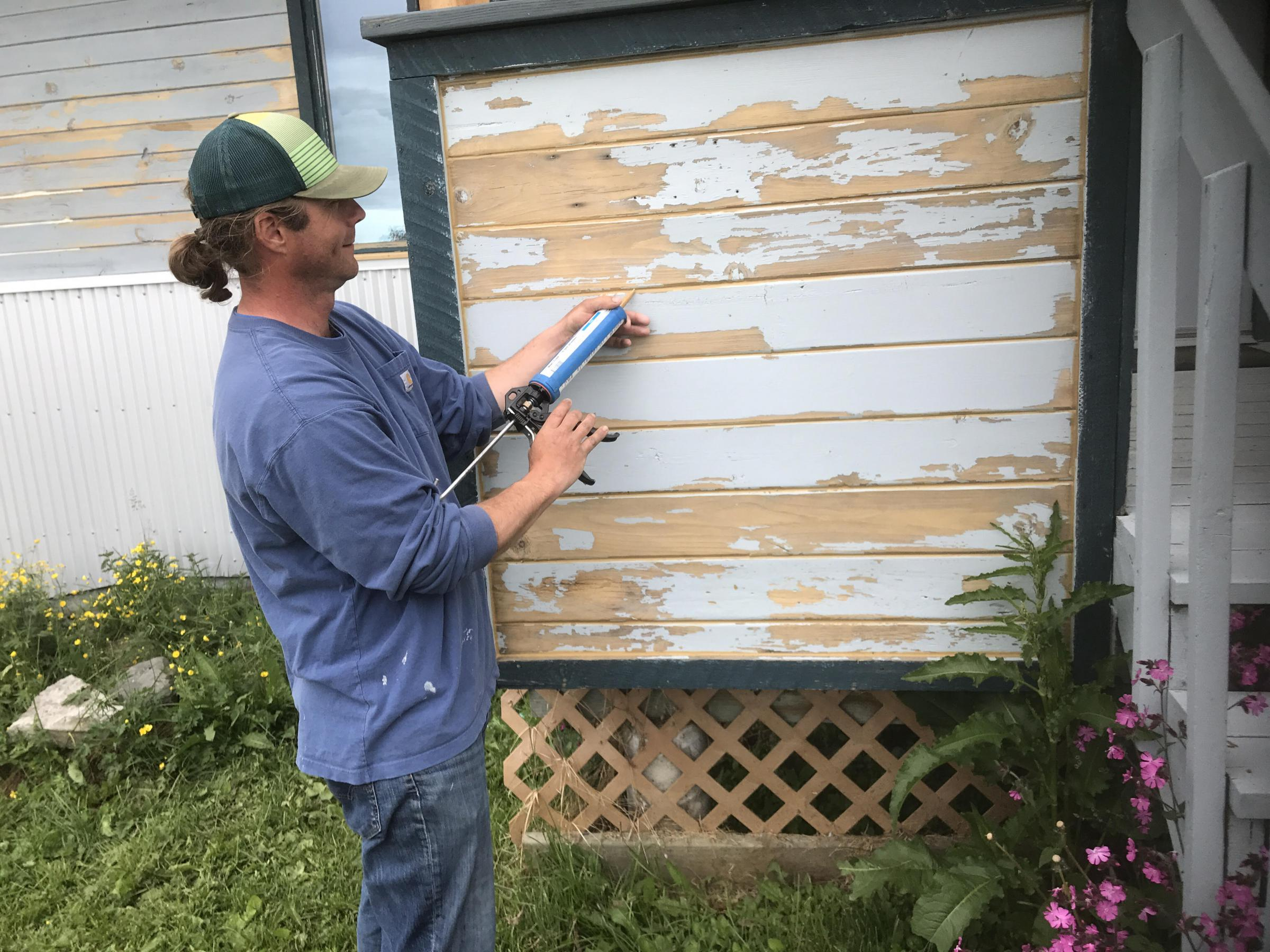 A contractor caulks siding before a new coat of paint is put on KBBI's exterior