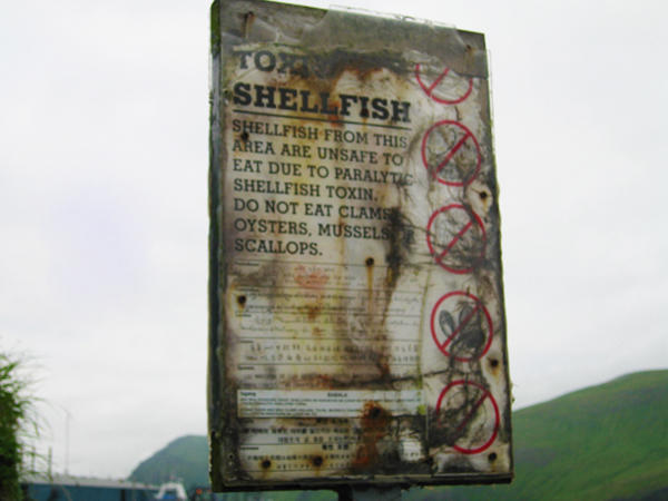 A sign warning people about the presence of the Paralytic Shellfish Poisoning (PSP) toxin, which can cause serious illness and death, posted by Trident Seafoods on an Akutan beach in the Aleutian Islands.