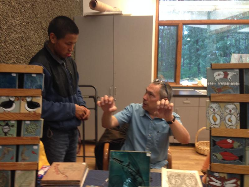 At the Alaska Native Heritage Center, Inupiaq artist Ed Mighell tells the story of the sea goddess Sedna to an intern, while displaying some of the tiles he creates.