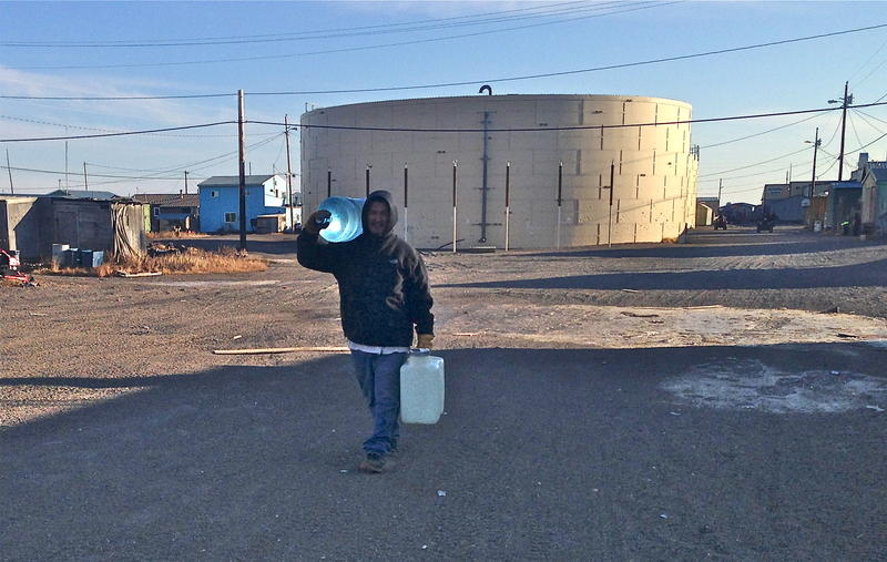 In about 100 rural Alaskan communities, people buy water from a central watering point, collect rain water, and haul water or ice from rivers or lakes. A 5-gallon jug of water, like the ones this young man in Kivalina is carrying, weighs about 40 lbs.