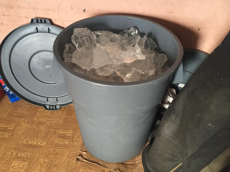 Ice is put into a plastic garbage can to melt.