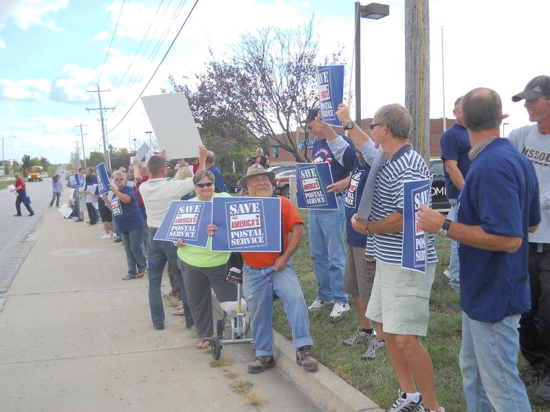 Postal workers rally outside of Blaine Luetkemeyer's office on Tuesday, September 27 to voice their opinions about the challenges facing the United States Postal Service.