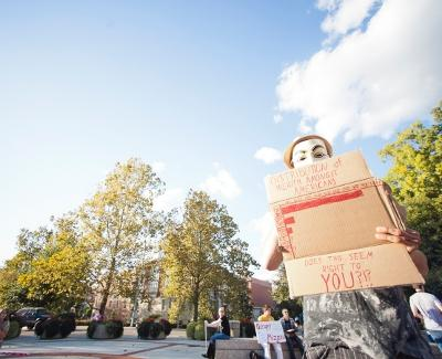 David McRae displays a sign while wearing a Guy Fawkes Mask Thursday for the Occupy Mizzou protest at Speakers Circle.