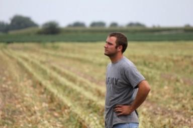 Austin Bruns, 25, watches as harvesters bring in corn crops in fields near his hometown of Beaver Crossing, Neb.