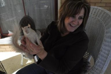Marionville Deputy Clerk Kathy Urschel holds up her white squirrel, Rocky.