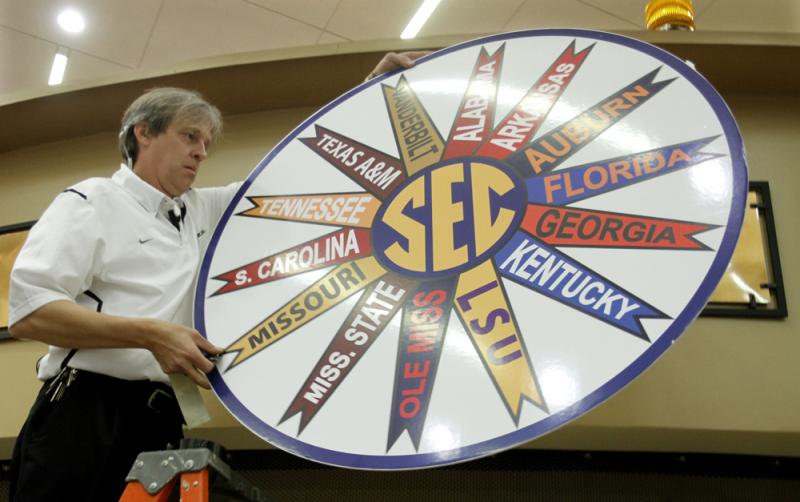 Daryle Bascom, director of Facilities and Events for the University of Missouri, hangs a banner with all 14 SEC conference team names just before the start of Sunday's announcement.