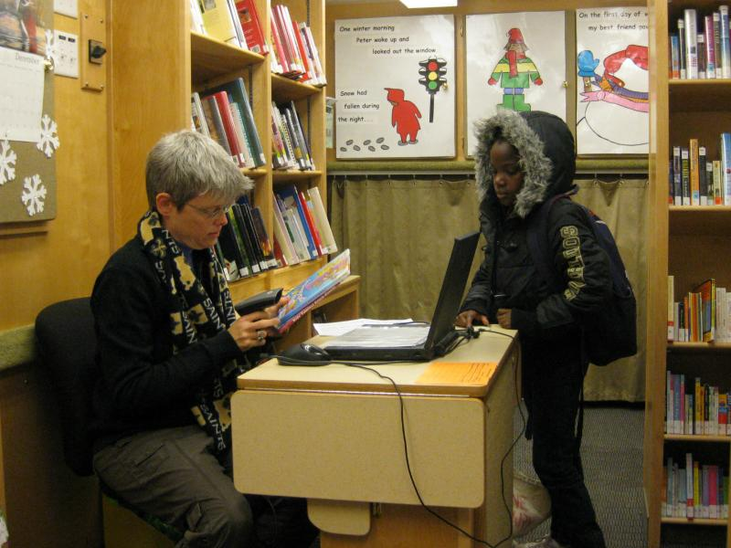 Inside Bookmobile, Jr. Otter Bowman helps a young client.