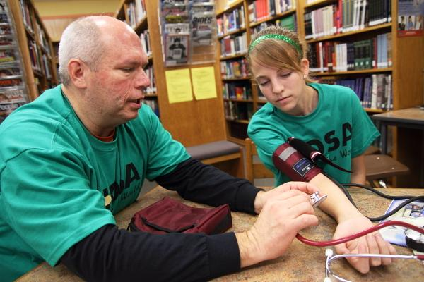 Dr. Dale Essmeyer shows Milan High student Kaylee Michael how to take blood pressure.