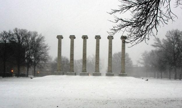 The columns of MU covered in snow.  A MU professor says the university can restructure how it spends its money.