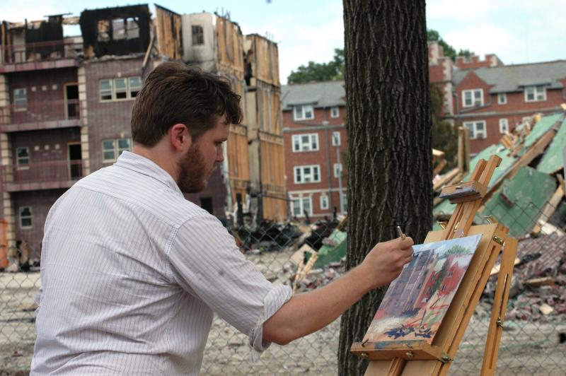 "Mark Nanneman paints the rubble of the burned Brookside on College apartment complex on Monday. Nanneman says he paints ""en plein air,"" a French style where the artist paints outdoors."