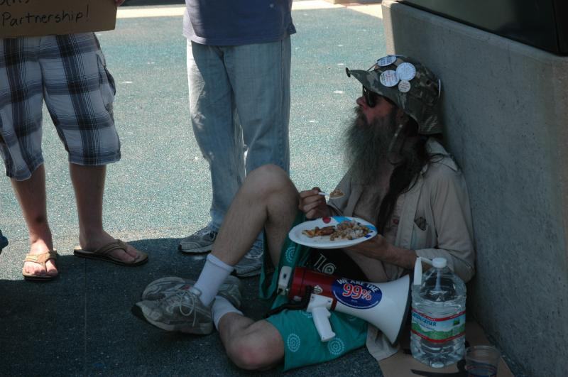 Activist Paul Searles sits in the shade as he eats a vegan meal of rice, beans and bread in front of City hall. He has been protesting in other movements for over 10 years.