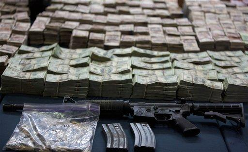 A captured assault rifle, and bundles of U.S. dollars and Mexican pesos are displayed during a media presentation in Mexico City.