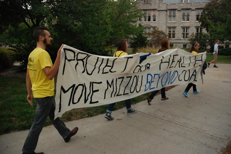 Demonstrators carry their banner into the MU Board of Curators meeting on Sept. 13 at the University of Missouri. Coal Free Mizzou is a student advocacy group asking UM Curators to phase out the use of coal.