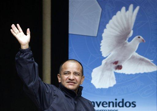 A former hostage waves to comrades before a press conference in Bogota. Earlier this year, Colombia's main rebel group freed what it says were its last 10 military and police captives.