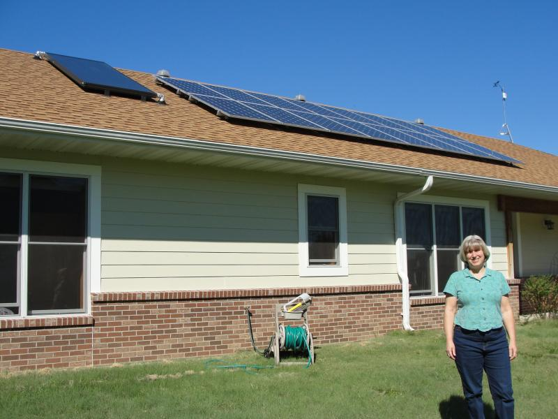 Judy McKinnon stands outside her energy efficient home in Fulton, Mo. McKinnon and her husband, Jim Stevermer, recently installed 16 solar electric panels on the roof.