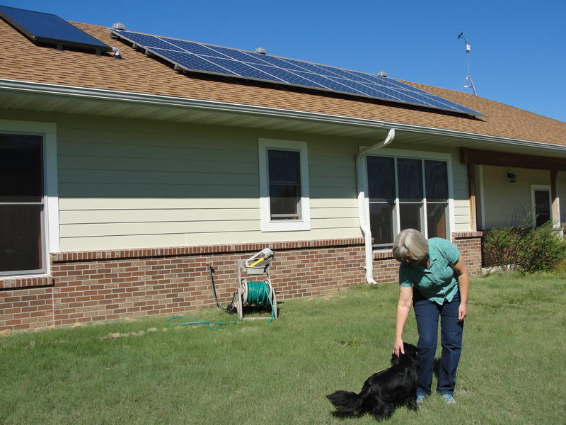 Judy McKinnon plays with her dog, Reggie, outside her energy efficient home in Fulton, Mo. McKinnon and her husband, Jim Stevermer, recently installed 16 solar electric panels on the roof.