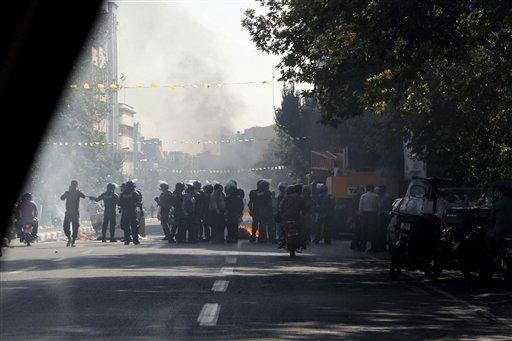 Iranian police officers block a street as garbage cans are set on fire, in central Tehran, on Wednesday, Oct. 3, 2012.