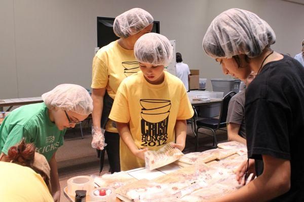 Allison Whittom, Jake Thompson and Jacob Stevens prepare to put packages of food in boxes.