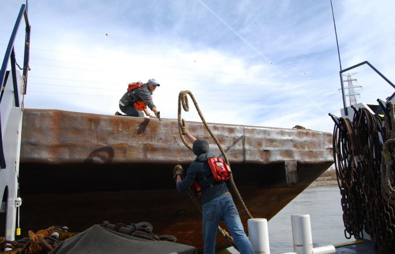 Experienced deckhand Billy Vanhorn catches hold of a rope before we check out an empty barge.