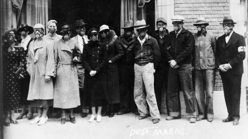 Residents of Liberal, Kansas pose in their gas masks in front of a Red Cross building in 1935. The masks were worn to protect their lungs from fine particles of blowing dust.