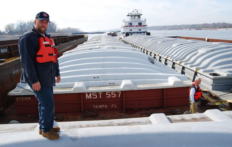 First mate Tyler Banicki stands atop a corn barge on a 20-barge flotilla headed to the Gulf of Mexico. To the right, Captain Ed Henleben checks out the Mississippi River. The R. Clayton McWhorter towboat in the rear will push these barges down river.