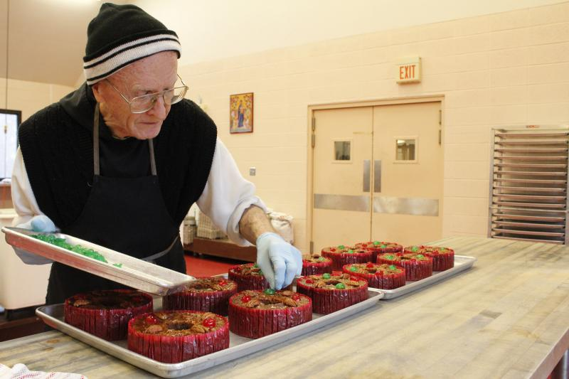 Father Cyprian Harrison, a Trappist monk, decorates fruitcakes in the bakery at Assumption Abbey in Ava, Mo. Each cake is topped with four pecan halves, two red cherries and two green cherries.