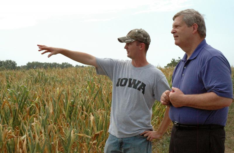Farmer Eric Cress, left, shows Agriculture Secretary Tom Vilsack the drought damage to his corn crop on his farm near Center Point, IA  in July 2012.
