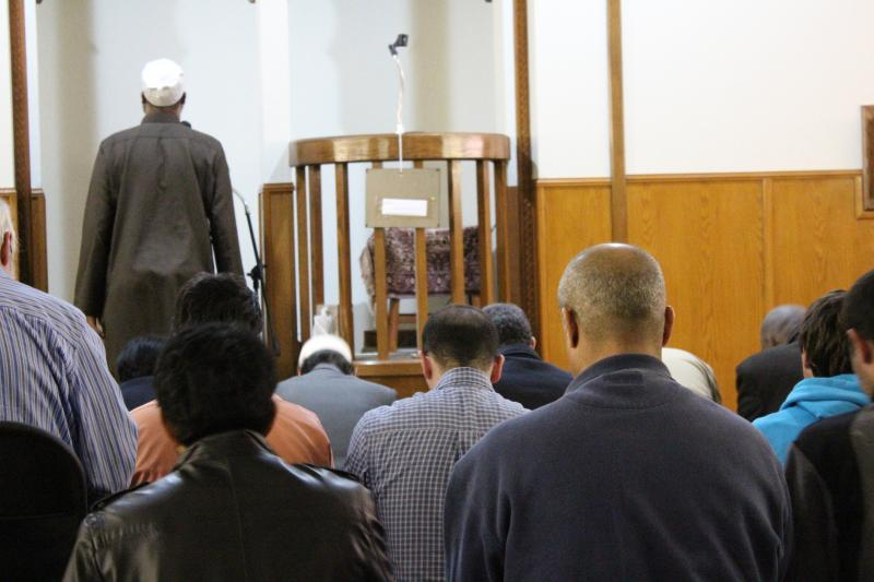 Men kneel in worship as another sings the call to prayer at the Islamic Center of Central Missouri. Even though the mosque does not have an official imam, or prayer leader and scholar, members of the community step up to perform the role, like the call to