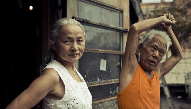 Noriko Shinohara (l.) looks in the camera as her husband Ushio stretches. From Zachary Heinzerling's CUTIE AND THE BOXER, a documentary about the 40-year marriage of artists Ushio and Noriko Shinohara.