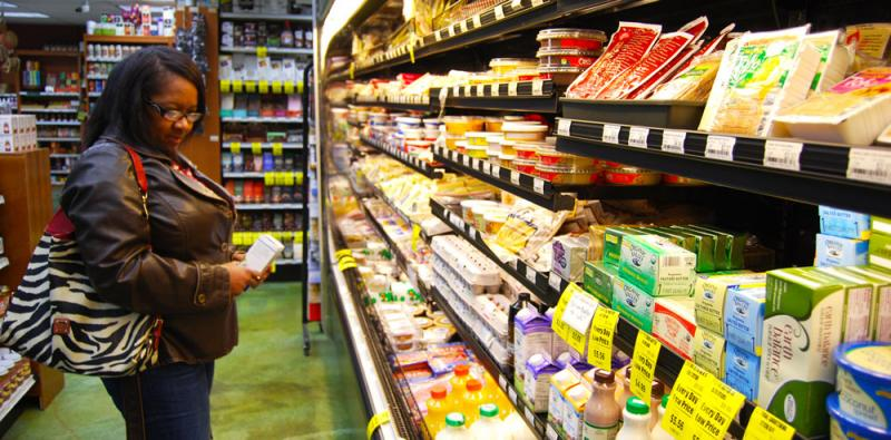"Kathy Lane, a regular at Clover's Natural Market in Columbia, Mo., looks over the store's cheese case. When asked if she would give raw milk cheese a try, she is uncertain: ""I would try it, but I'm not sure."""
