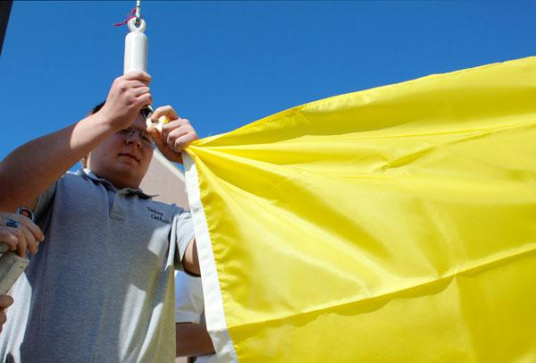 Ian McMurtry clips the papal flag onto the flag pole. The school hadn't been flying a papal flag since Benedict XVI resigned on Feb. 28.