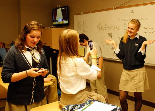 Sophie Spicci texts her public school friends about the new pope, while Emily Temple takes a picture of Kristen Schepker after braiding her hair.