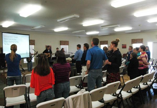 The congregation of LifeBridge Lutheran Church sings along to a worship song in the community building of Hanover Estates in Columbia, Mo. Sunday, April 21.