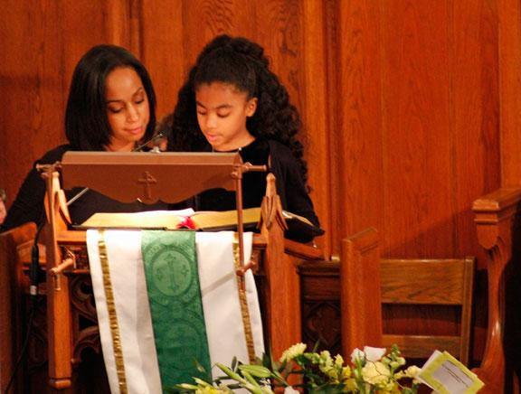 Alexis and Joi Battle read a Bible passage from the book of Ecclesiastes at the Celebration of Life for their grandfather, Eliot Battle.