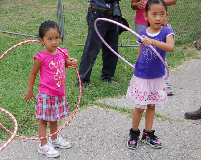 "Two girls from a family of Burmese refugees learn how to use a hoola hoop on Saturday at Columbia World Refugee Day at Broadway Christian Church.  ""We only speak to them Burmese at home.  We don't want them to forget their culture,"" said their mother Vung"