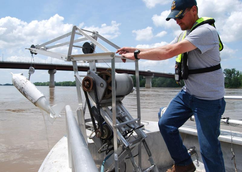 Joe Schatz, a hydrologist with the U.S. Geological Survey, cranks up a sample of Missouri River water near Hermann, Mo.