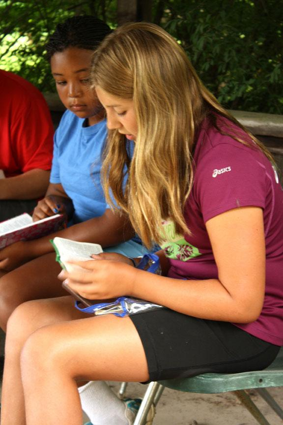 "Madeline Appel, 11, reads a passage from the Bible during Reflections on the Water at Camp Jump Start. Davis gives all the credit for being at camp to God. ""God helped me come and if it wasn't for him I wouldn't be here,"" Davis said."