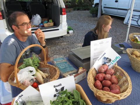 At a farmer's market in Lawrence, Kan., science teacher Perry Kennard and student Claire Yackley sell produce from Southwest Middle School's garden.