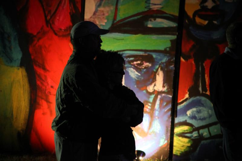 A couple listens to Trombone Shorty in front of a lit-up art piece on Saturday night.