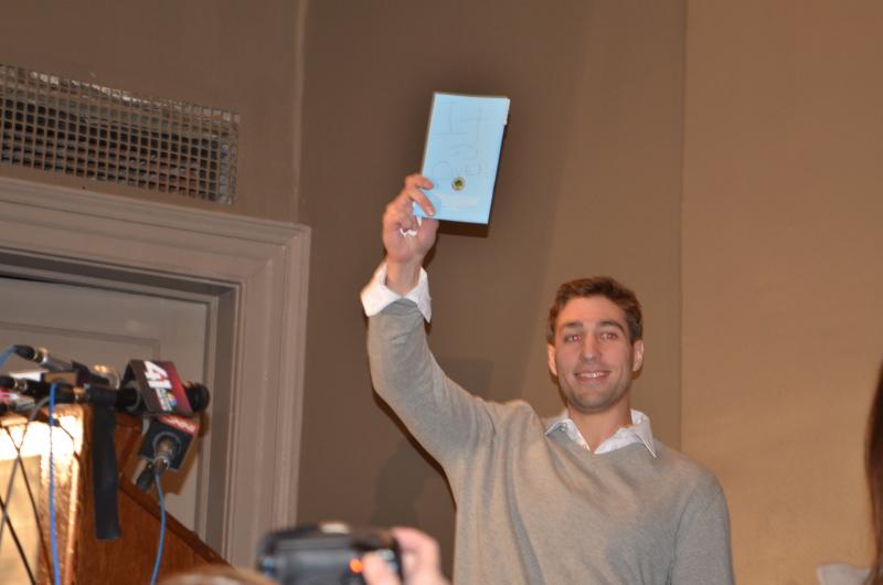 "Ryan Ferguson holds up the sign that his attorney Kathleen Zellner showed him through prison glass earlier in the day on Nov. 12, 2013.  It reads, ""It is over!"""