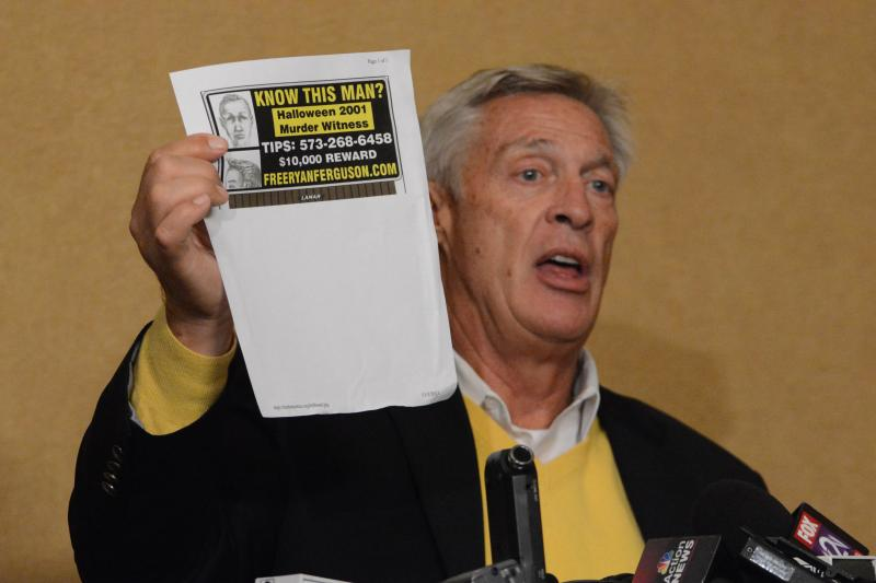 Bill Ferguson holds up a composite sketch of a witness to the Heitholt murder at a press conference on November 5, 2013