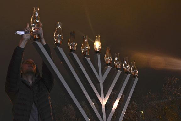 An MU student helps light a giant menorah on Wednesday night during a celebration marking the end of Hanukkah.