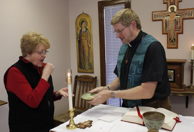 Fr. John Prenger gives Eucharist to Betty Ham at a midday liturgy.
